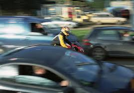 Image shows motorcycle filtering through traffic